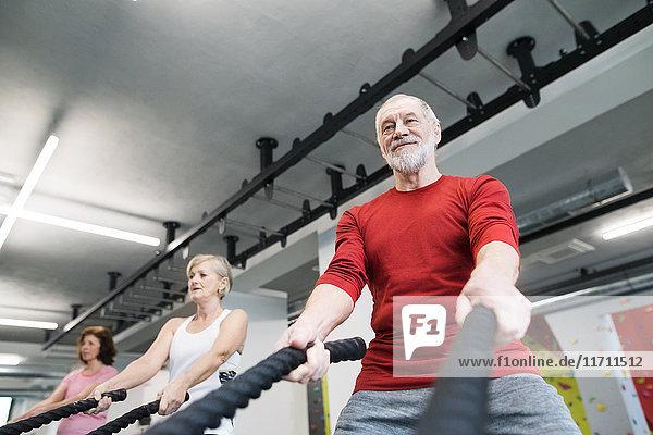 Senioren in der Turnhalle trainieren mit Kampfseilen