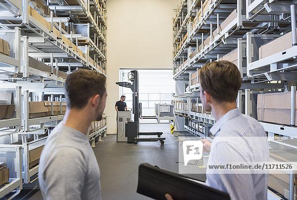 Zwei Männer mit Dokumenten und Arbeiter mit Gabelstapler im Werkslager