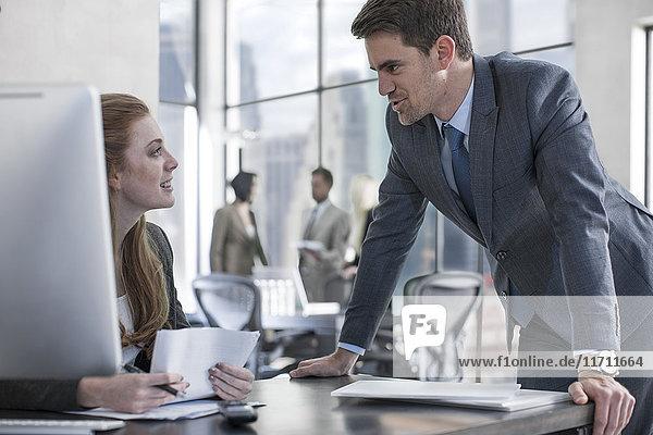 Geschäftsmann im Gespräch mit Frau am Schreibtisch
