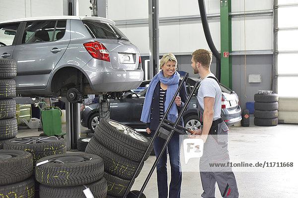 Kfz-Mechaniker mit Kunde und Reifen in der Werkstatt