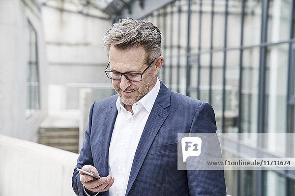 Lächelnder Geschäftsmann beim Blick auf sein Handy