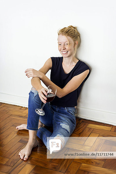 Ginger woman sitting on floor at home  drinking red wine