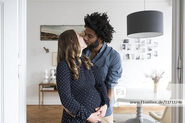 Küssen eines schwangeren Paares im Wohnzimmer