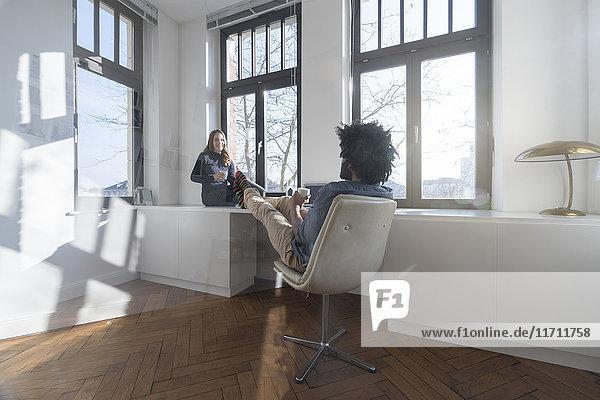 Lächelndes Paar  das in einem minimalistischen  leeren Raum sitzt und redet.