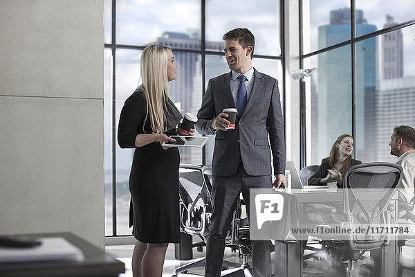 Geschäftsmann mit Kaffee im Gespräch mit Frau im Stadtbüro