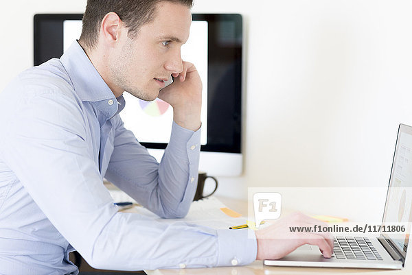 Geschäftsmann am Telefon mit Laptop