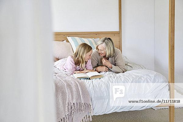 Kleines Mädchen auf dem Bett liegend mit ihrer Großmutter im Gespräch