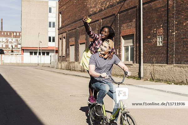Young couple riding bicycle in the street  woman standing on rack  taking selfies