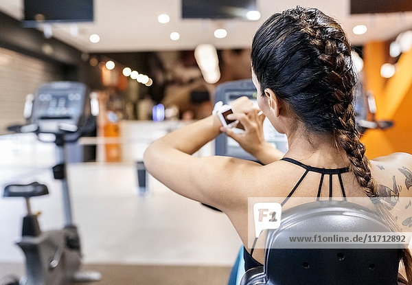 Woman using her smartwatch in gym