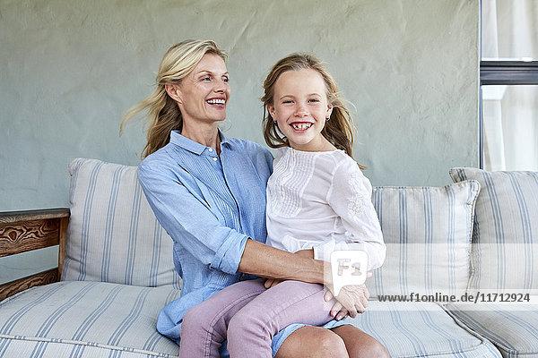 Porträt des lächelnden Mädchens auf dem Schoß der Mutter