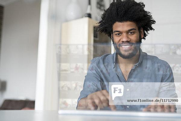 Lächelnder Mann zu Hause bei der Arbeit am futuristischen Bildschirm