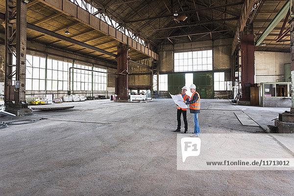 Zwei Männer mit Plan  die Sicherheitswesten tragen  reden in der alten Industriehalle.