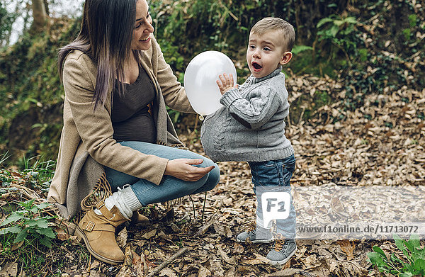 Happy pregnant mother and little boy having fun with a balloon in forest