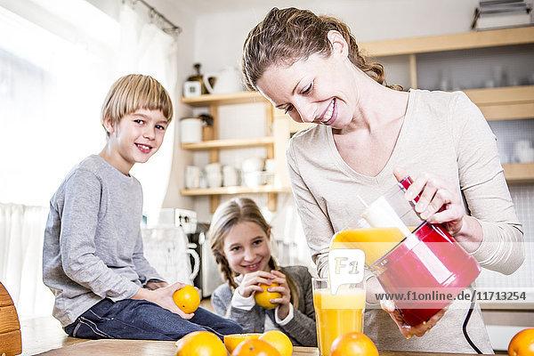 Frau gießt frisch gepressten Orangensaft ins Glas für Kinder