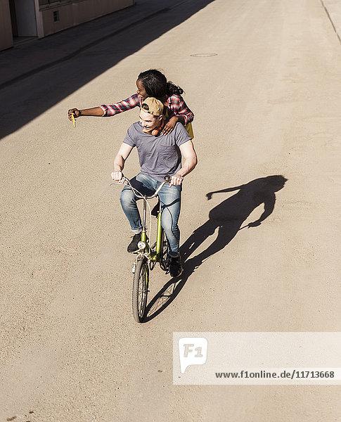 Junger Mann auf dem Fahrrad mit seiner Freundin  die auf einem Gestell steht und sich selbst nimmt