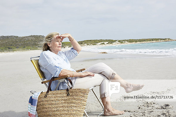 Senior woman sitting on the beach  looking at distance