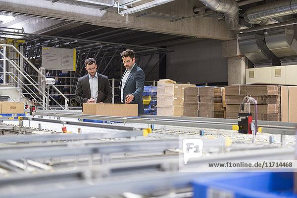 Zwei Geschäftsleute im Gespräch am Fließband in der Fabrik