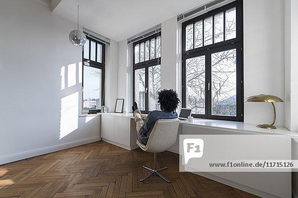 Mann sitzt im minimalistischen leeren Raum auf Stuhl