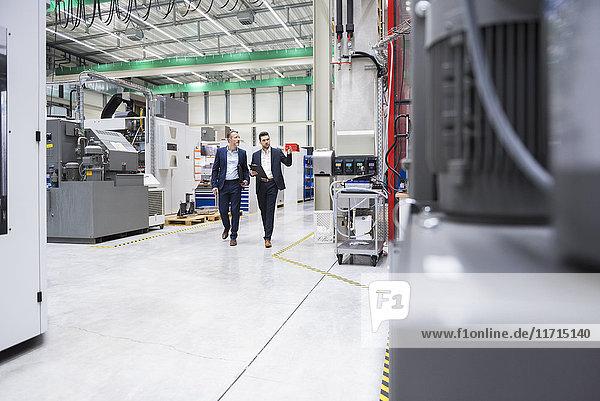 Zwei Männer gehen und reden in der Fabrikhalle.