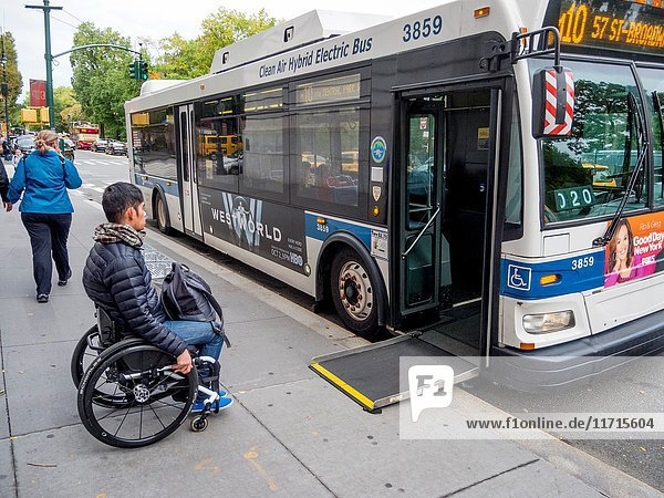 A city bus extends a handicapped ramp for a wheelchair user at a bus stop on Central Park West in New York City.