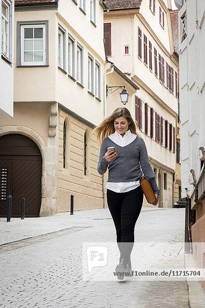 Deutschland  Tübingen  lächelnder junger Student beim Gehen auf das Handy schauen
