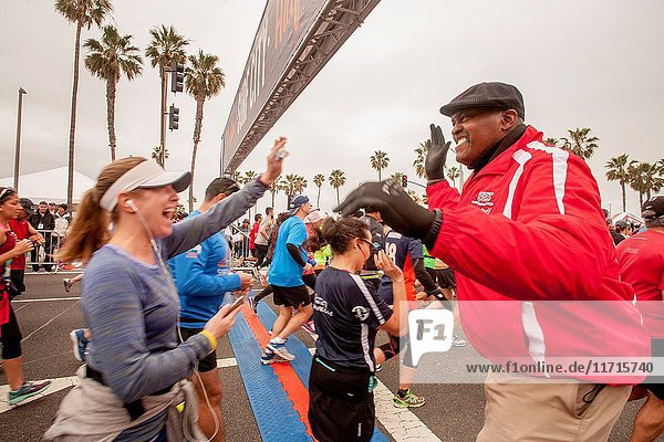 An enthusiastic spectator offers a high five to encourage a marathon runner in Huntington Beach  CA.