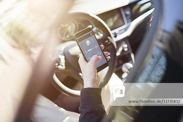 Mann im Auto Einstellgeräte zu Hause über Smartphone