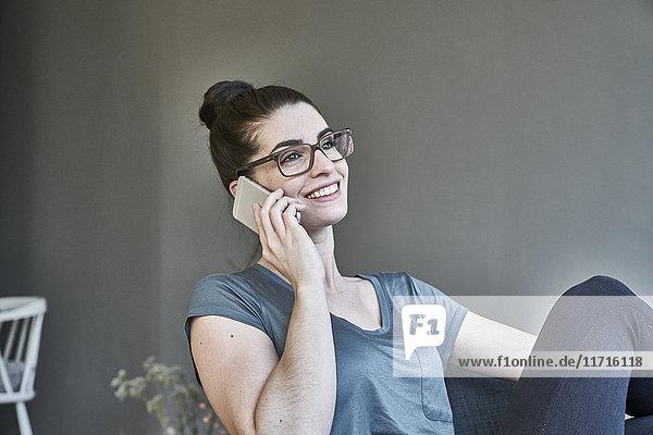 Lächelnde junge Frau spricht am Handy