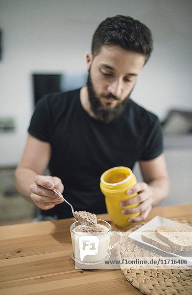 Junger Mann  der sein Frühstück zu Hause zubereitet und Kakao und Milch mischt.