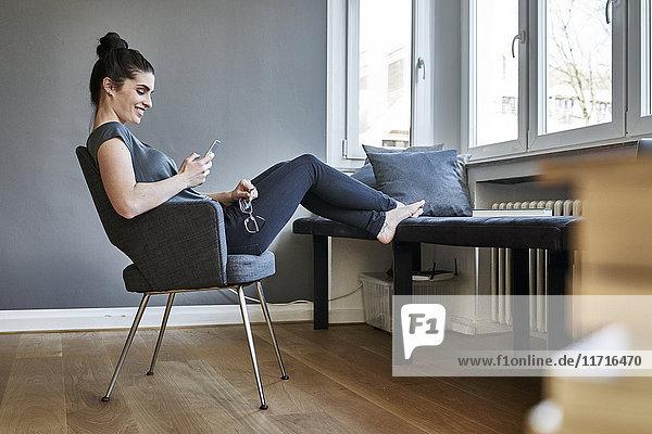 Lächelnde junge Frau mit dem Handy zu Hause