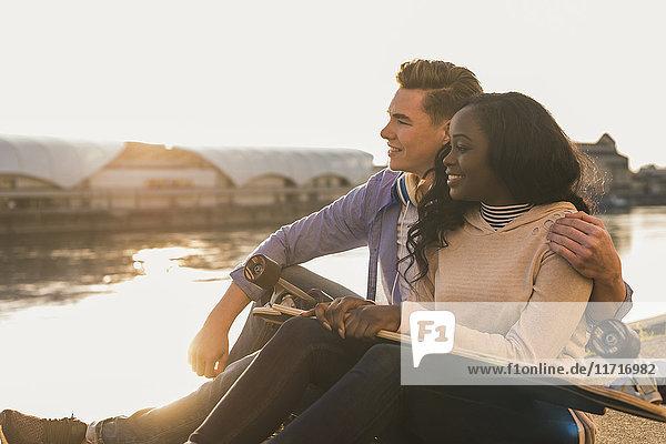 Junges Paar sitzt am Fluss und schaut dem Sonnenuntergang zu.