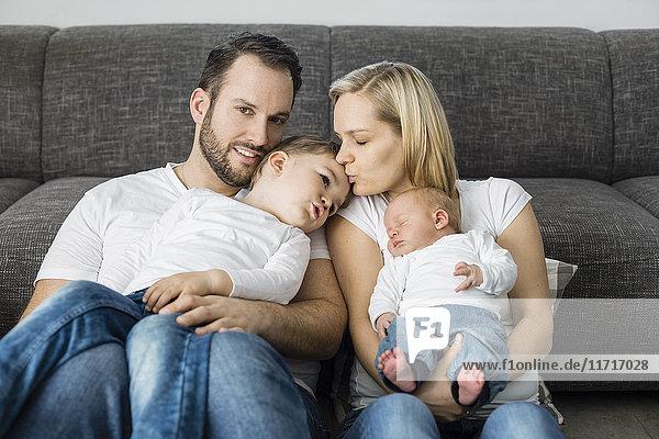 Eltern mit männlichem Neugeborenen und kleinem Sohn  die sich zu Hause entspannen.