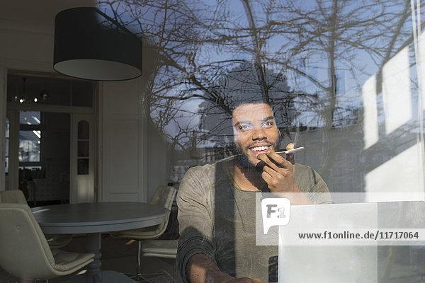 Mann spricht auf dem Smartphone vor dem Laptop am Fenster