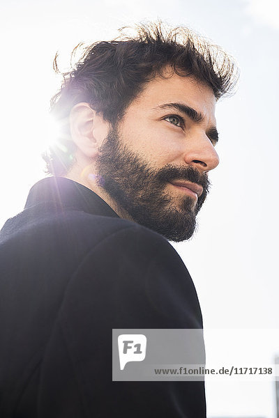 Portrait of young man with full beard at backlight