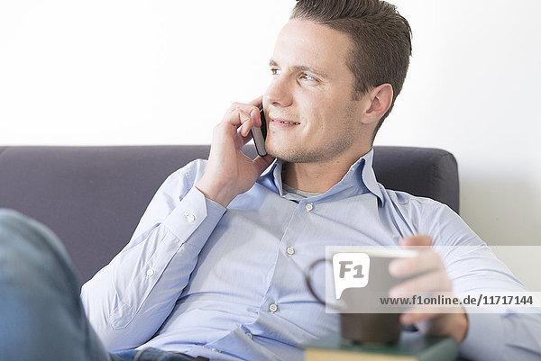 Lächelnder Geschäftsmann auf der Couch mit Smartphone und Tasse Kaffee