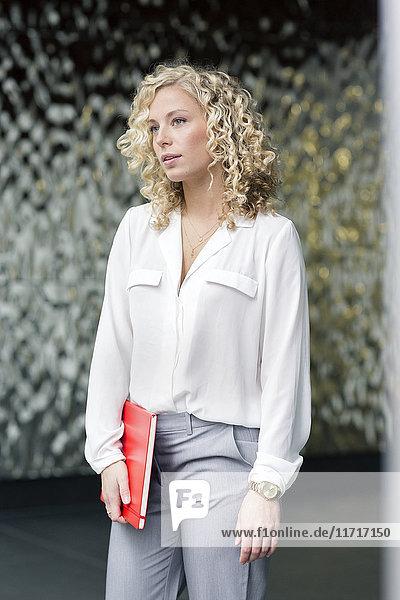 Porträt einer blonden Geschäftsfrau mit Notizbuch im Foyer