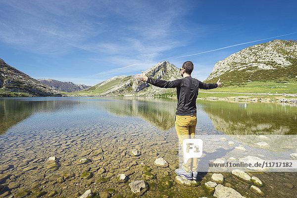 Spanien  Asturien  Picos de Europa Nationalpark  Mann mit erhobenen Armen an den Seen von Covadonga