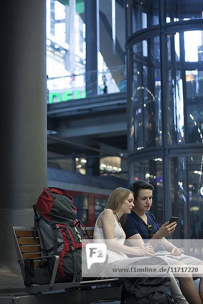 Junges Paar mit Rucksäcken am Bahnhof mit Smartphone