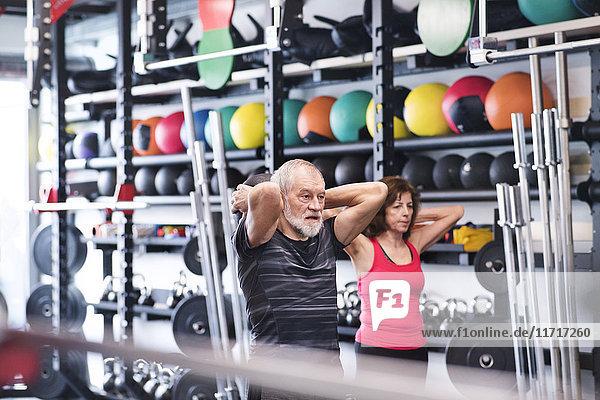Senior Mand und Frau im Fitnessstudio mit Medizinbällen