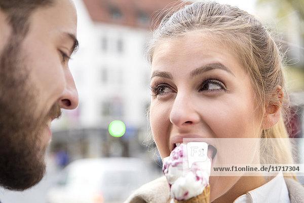 Porträt einer jungen Frau  die mit ihrem Freund Eis isst.