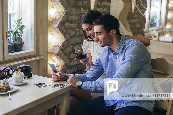 Junges Paar beim Betrachten von Sofortbildern in einem Restaurant
