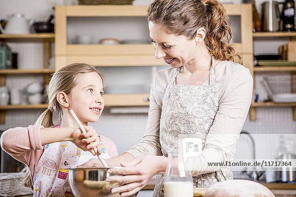 Mother and daughter baking in kitchen together