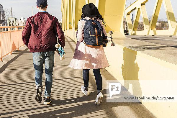 Junges Paar mit Skateboard auf der Brücke