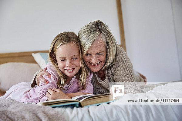 Kleines Mädchen auf dem Bett liegend mit ihrer Großmutter  die ein Buch liest.