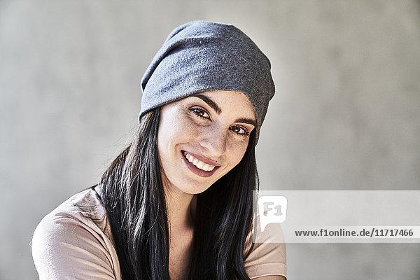 Porträt einer lächelnden jungen Frau mit Mütze