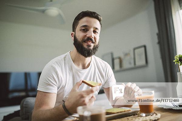 Porträt eines jungen Mannes beim Frühstück
