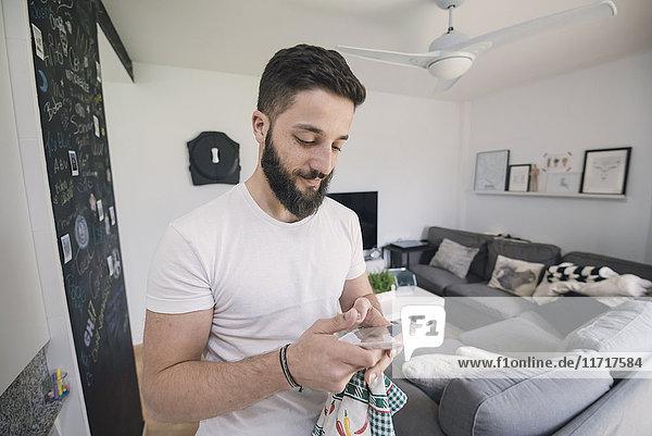Junger Mann mit seinem Smartphone zu Hause