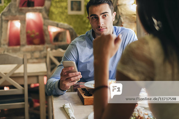 Man with cell phone face to face with his girlfriend in a restaurant