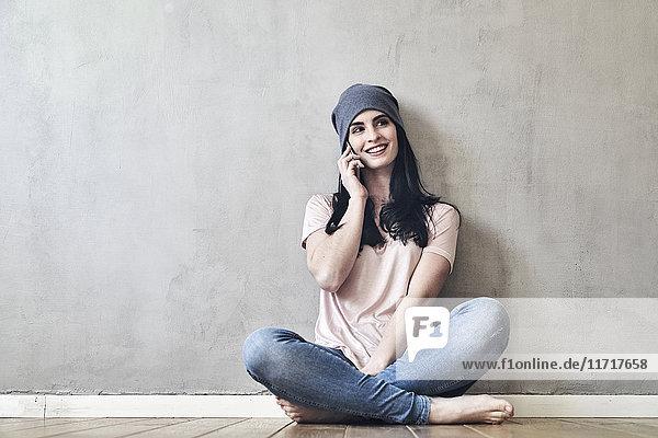 Lächelnde junge Frau sitzt auf dem Boden und redet am Handy.