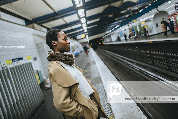 Junge Frau wartet am Bahnsteig der U-Bahn-Station
